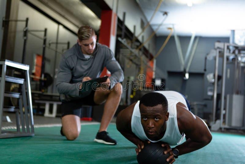 Escritura masculina del instructor en el tablero mientras que ejercicio atlético masculino con la bola del ejercicio foto de archivo libre de regalías