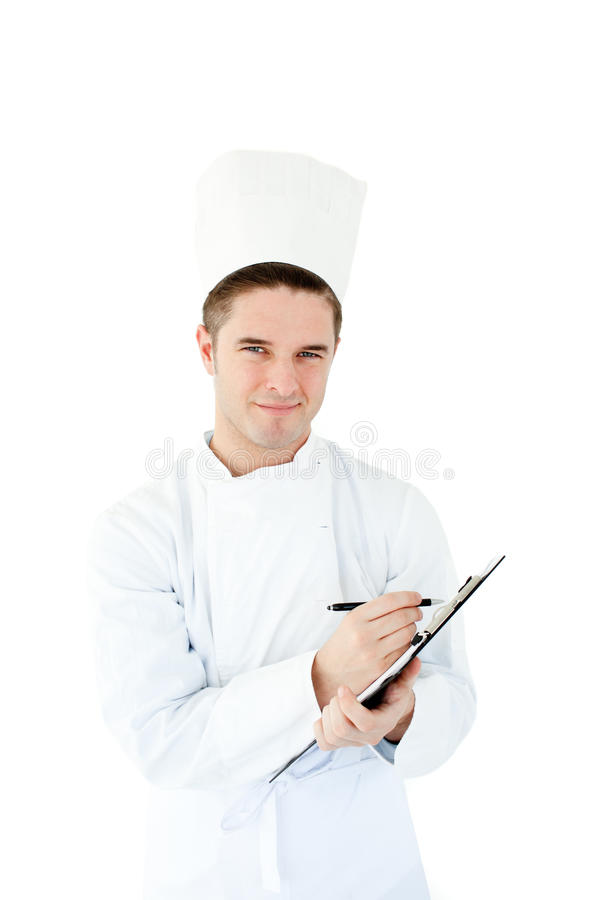 Escritura masculina joven alegre del cocinero en un sujetapapeles imagen de archivo