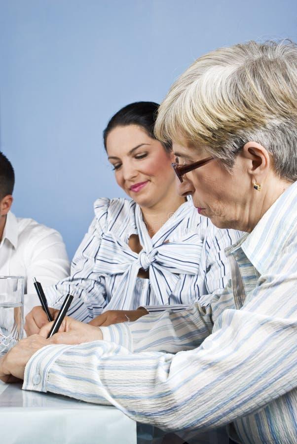 Escritura mayor de la mujer de negocios en la reunión imagen de archivo