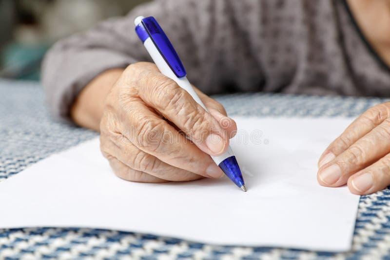 Escritura mayor de la mujer en el papel en blanco fotos de archivo