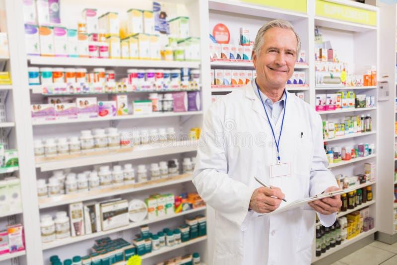 Escritura mayor sonriente del farmacéutico en el tablero foto de archivo libre de regalías