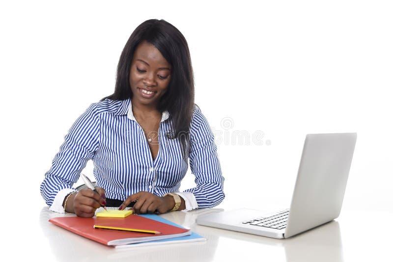 Escritura negra atractiva y eficiente de la mujer de la pertenencia étnica en la libreta en el escritorio del ordenador portátil  fotos de archivo libres de regalías