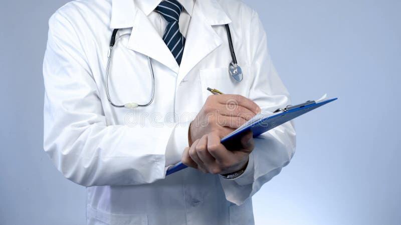 Escritura profesional del médico en los documentos de papel, guardando informes médicos imagen de archivo