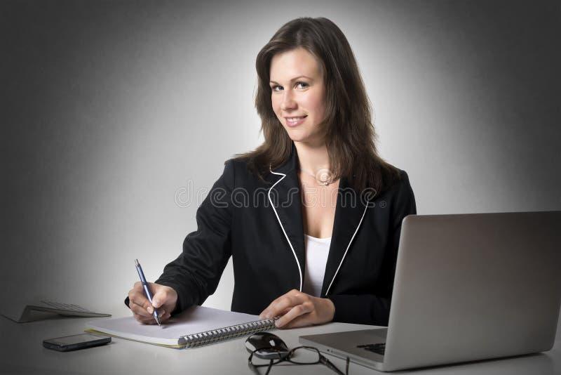 Escritura sonriente de la empresaria algo imagen de archivo