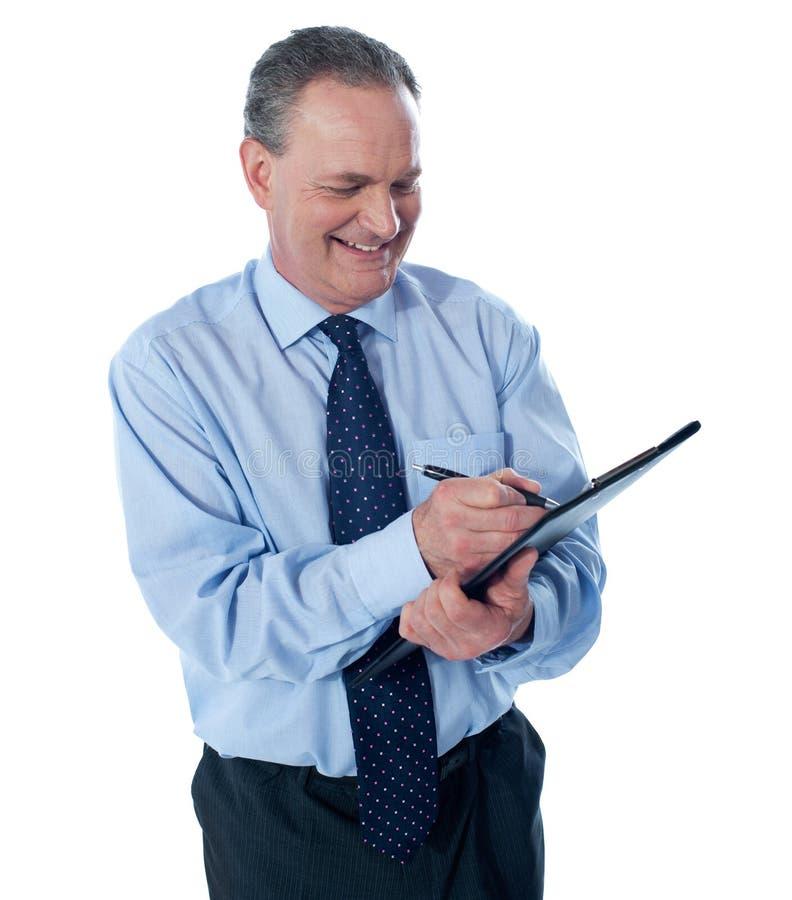 Escritura sonriente del hombre de negocios en el sujetapapeles imagen de archivo