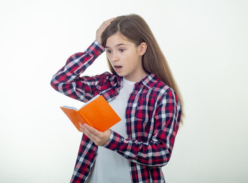 Escritura sorprendida de la chica joven en cuaderno usando el lápiz, manteniendo la boca abierta de par en par imagenes de archivo