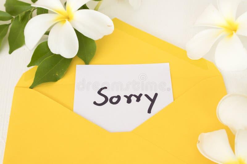 Escritura triste de la tarjeta del mensaje en sobre amarillo con las flores del frangipani imagenes de archivo