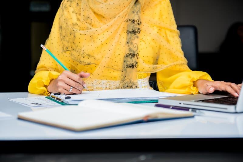 Escritura y muestra musulmanes de las empresarias en el papel fotografía de archivo
