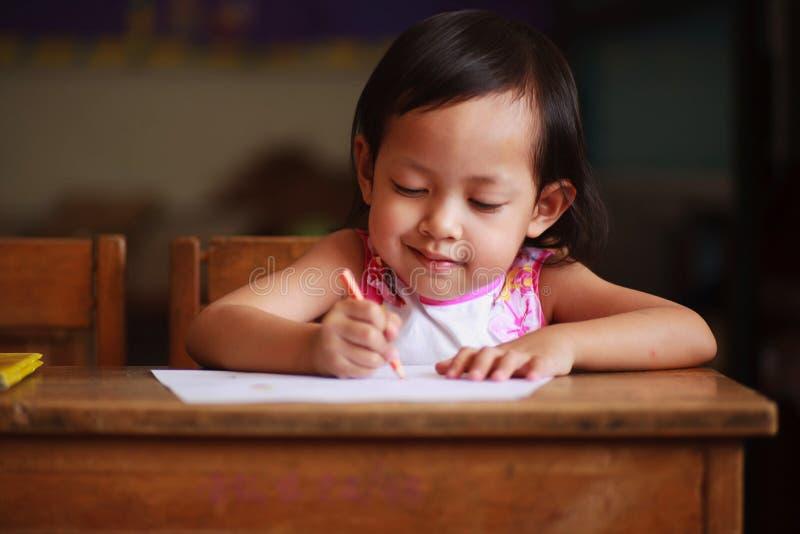 Escritura y sonrisa del niño imágenes de archivo libres de regalías