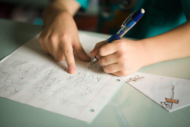 Escritura zurda del muchacho foto de archivo