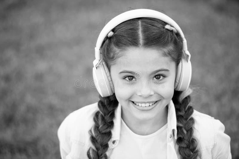 Escucha la m?sica mientras que se relaja al aire libre La muchacha del ni?o disfruta de m?sica mientras que si?ntese en prado de  fotos de archivo libres de regalías