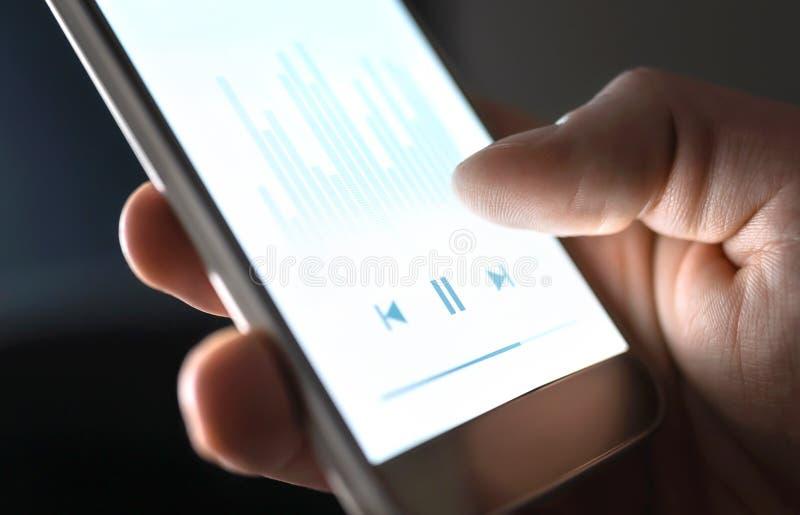 Escuchando para hacer un podcast, música o audiolibro con el teléfono móvil Hombre usando fluir el app del servicio y del smartph fotografía de archivo