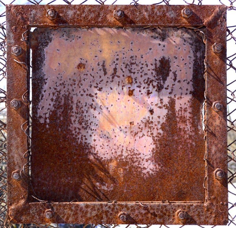 Escudo oxidado del hierro con los pernos foto de archivo