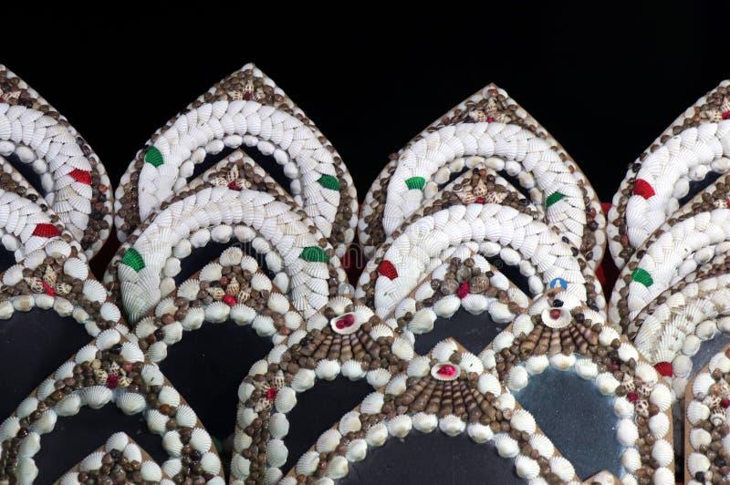 Escudos do búzio no mercado da noite da praia do mar de Puri Espelho no fundo preto fotografia de stock royalty free