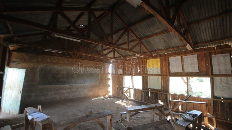 Escuela africana Pequeño pueblo pobre, alumnos que se sientan en las tablas fotografía de archivo libre de regalías