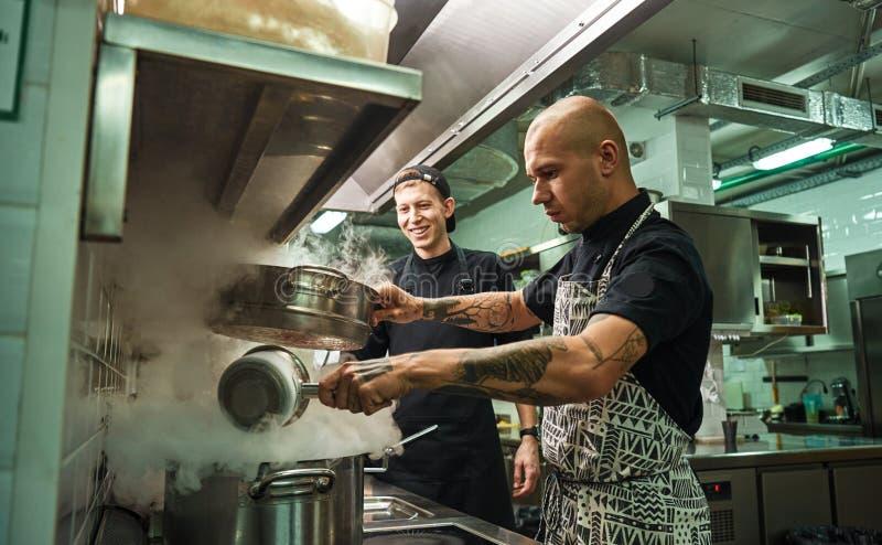 Escuela culinaria Cocinero hermoso y confiado que enseña a cómo cocinar a sus dos ayudantes en una cocina del restaurante imagen de archivo libre de regalías