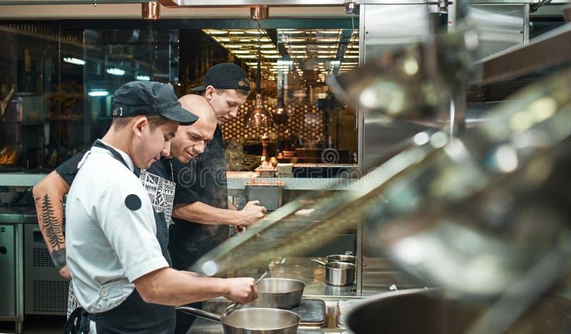 Escuela culinaria Cocinero joven estricto en el delantal que mira cuidadosamente cómo su cocinar auxiliar la cocina del restauran fotos de archivo libres de regalías