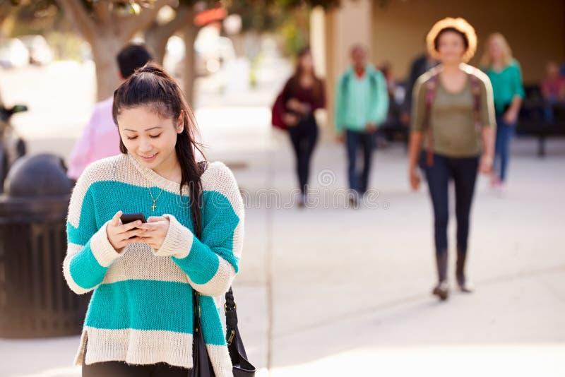 Escuela de Walking To High del estudiante usando el teléfono móvil imagen de archivo libre de regalías