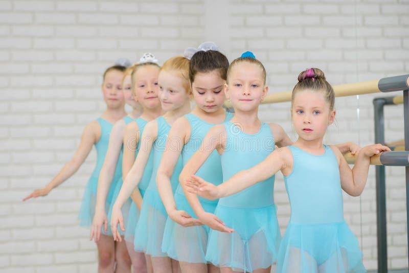 Escuela del ballet Estudiantes de las niñas que practican cerca de la barra Tiro medio de bailarinas en clase de danza foto de archivo libre de regalías