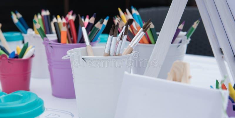 Escuela del dibujo del ` s de Nchildren, creatividad del ` s de los niños con los cepillos y primer de los rotuladores imagenes de archivo
