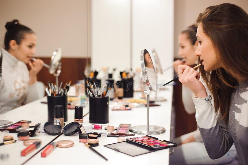 Escuela del maquillaje Componga al artista que hace al profesional para componer de mujer joven Escuela de la belleza foto de archivo libre de regalías