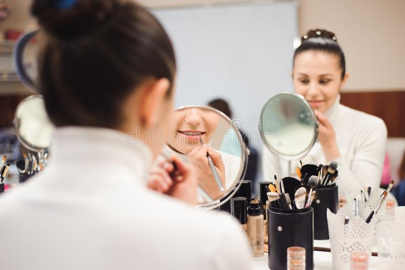 Escuela del maquillaje Componga al artista que hace al profesional para componer de mujer joven Escuela de la belleza foto de archivo