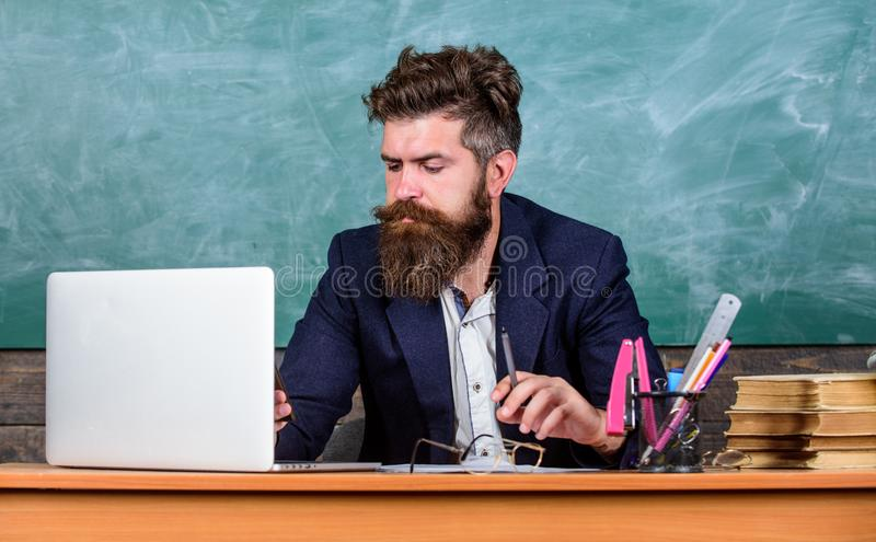 Escuela en línea y educación Concepto que enseña distante El hombre maduro barbudo del profesor enseña en línea usando el ordenad foto de archivo libre de regalías