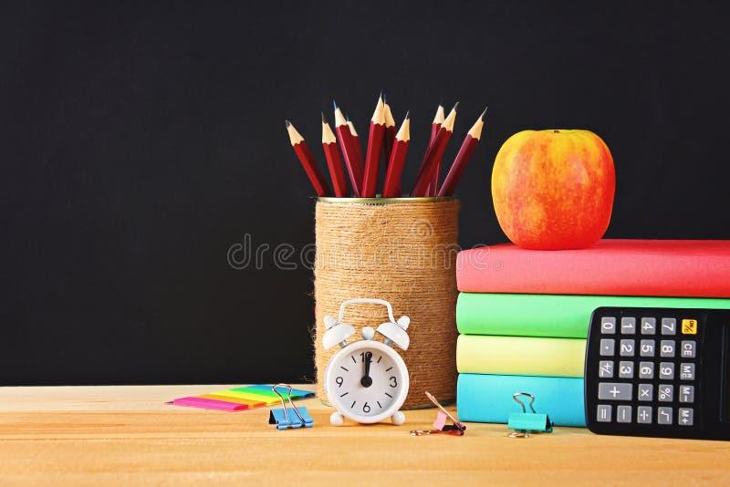 Escuela y materiales de oficina en un fondo negro de la pizarra De nuevo a escuela foto de archivo