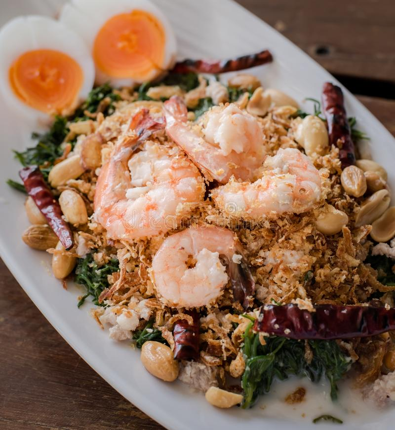 Esculentum Vegetable fern spicy salad with eggs and shrimp in coconut milk topping with peanut. Thai food name `Yum Pak Goot` is a esculentum Vegetable fern royalty free stock images