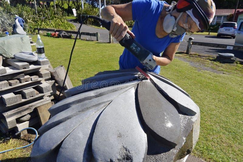 Escultor de piedra del artista que talla esculpiendo el pedazo enorme del arte del helecho de plata de Nueva Zelanda fotos de archivo