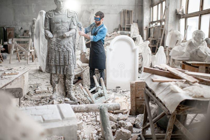 Escultor que trabaja con la escultura en el estudio foto de archivo libre de regalías