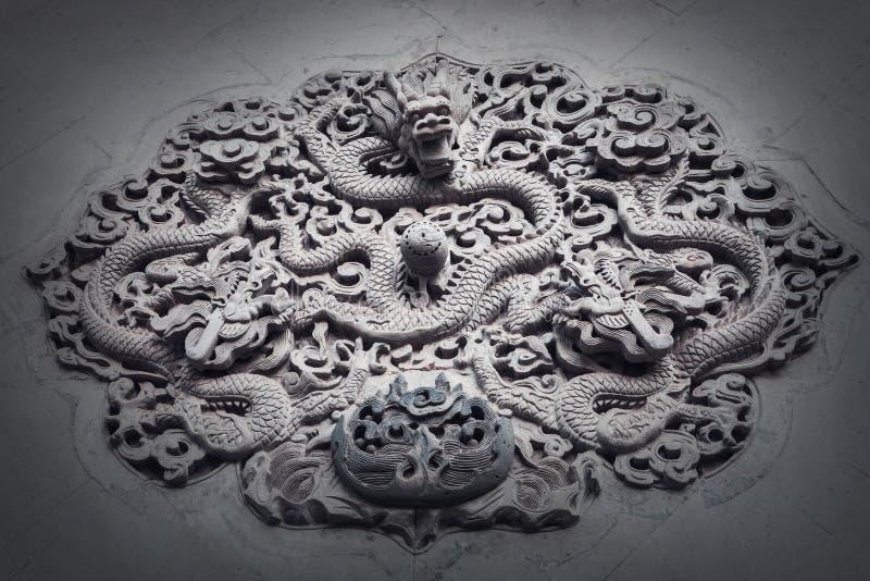Escultura adornada del bajorrelieve del dragón en la pared. foto de archivo