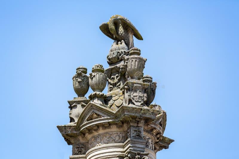 Escultura al aire libre adornada del águila que alimenta joven encima de pilar grande fuera de la catedral en Autun, Borgoña, Fra foto de archivo
