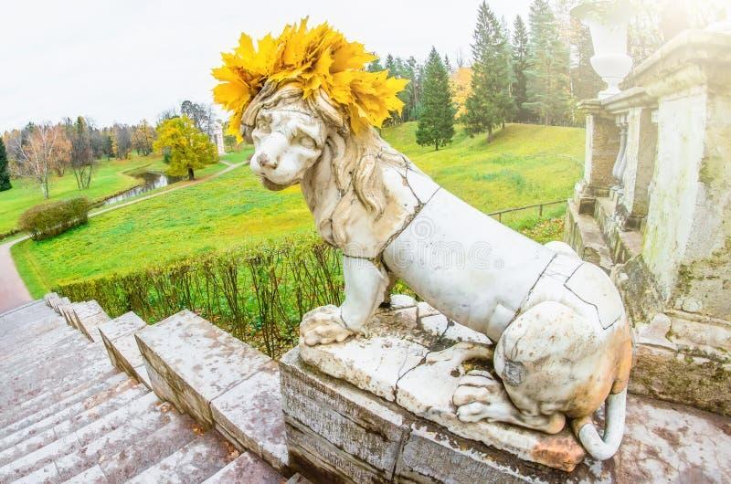 Escultura antigua de un león con las hojas de arce en su cabeza en un parque del otoño fotos de archivo