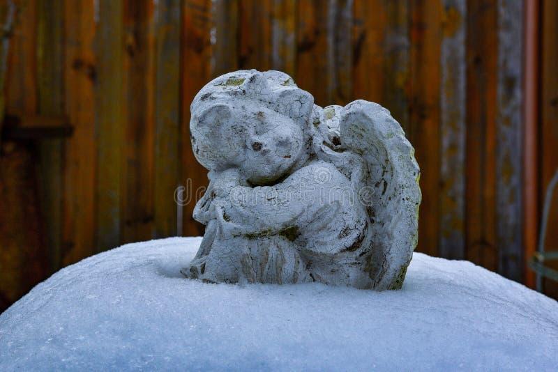 Escultura blanca de la piedra de un pequeño ángel que se sienta en la nieve fotos de archivo
