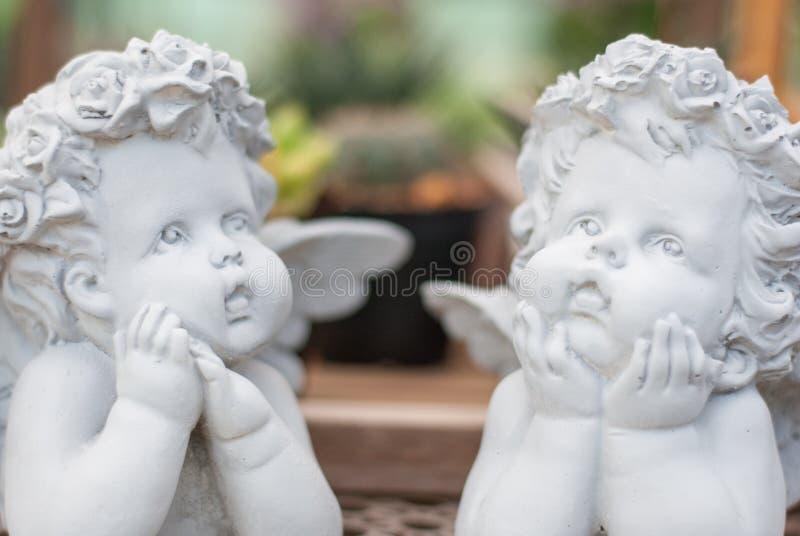 A escultura branca de dois meninos do cupido feita do cimento consiste na ação de pensamento e na vista ao céu imagens de stock
