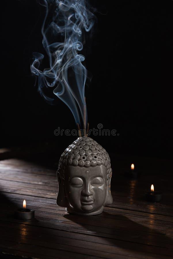 Escultura da cabeça de buddha com as varas e velas ardentes do incenso fotos de stock royalty free