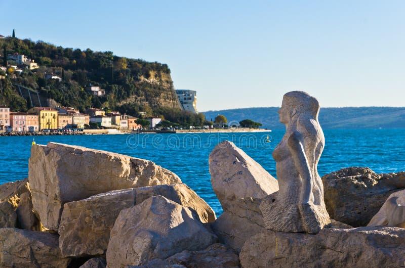 A escultura da sereia cinzelou fora das rochas de pedra no porto de Piran, Istria imagens de stock