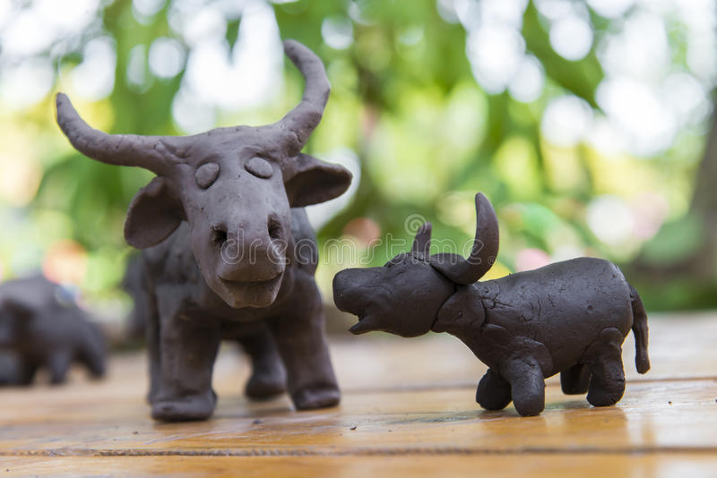 escultura de arcilla del búfalo del padre y del hijo en fondo de madera en el ou foto de archivo
