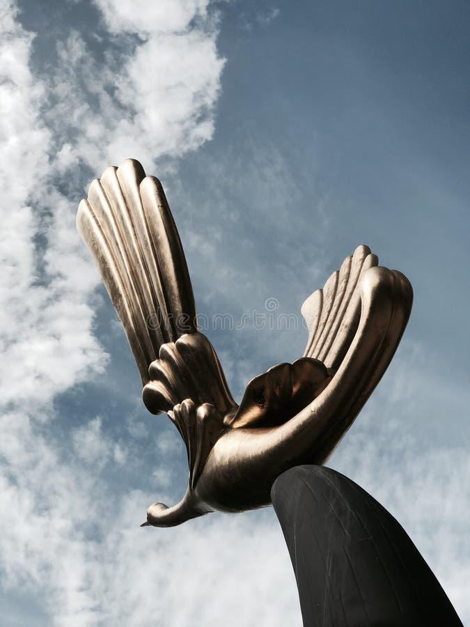 Escultura de bronce de un pájaro contra el cielo azul foto de archivo