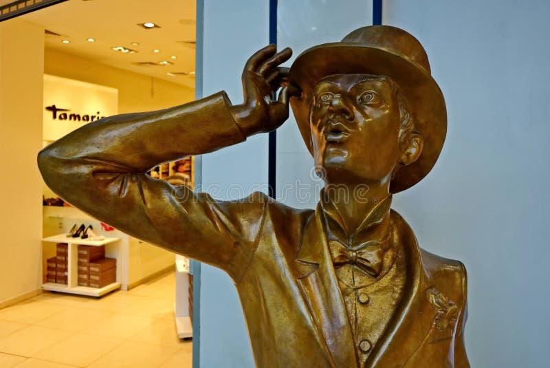 Escultura de bronze 'cavalheiro ' O cavalheiro inclina-se em seu bastão e guarda-se seu cilindro com seu assistente Instalado em  fotos de stock