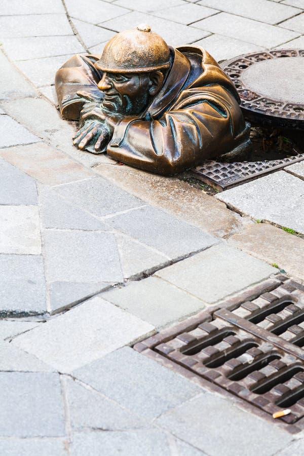 Escultura de bronze de Cumil o Peeper em Bratislava foto de stock