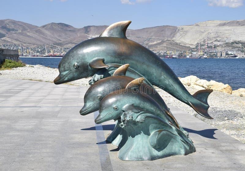 A escultura de bronze de três golfinhos na praia fotos de stock