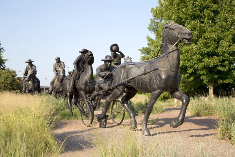 A escultura de bronze do grupo na terra centenária corre o monumento foto de stock