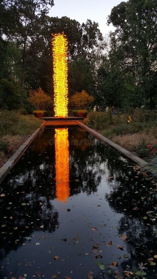 Escultura de cristal de Chihuly en amarillo y rojo con la piscina de la reflexión del agua fotos de archivo