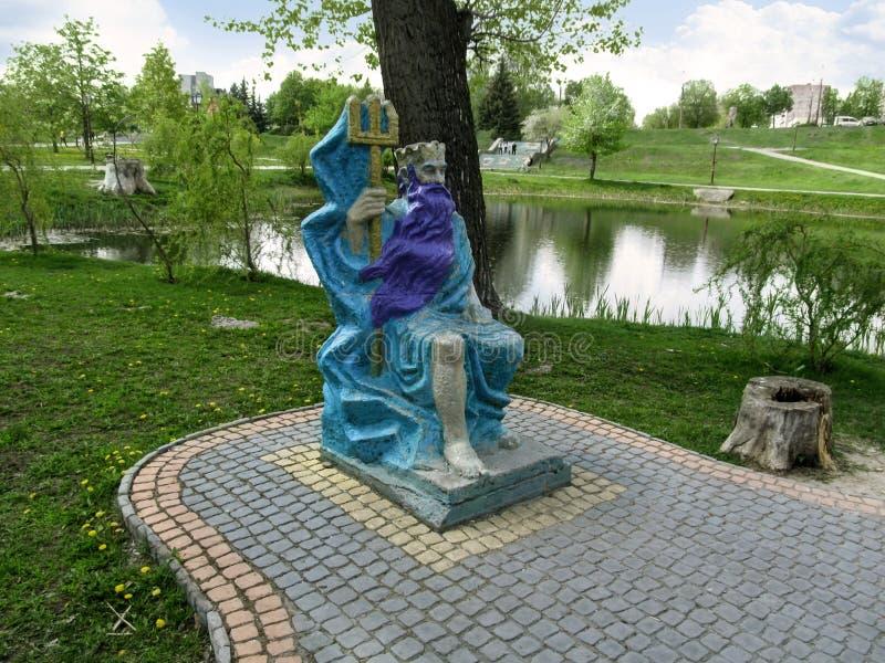 Escultura de dios Poseidon del griego cl?sico en el banco de la charca en el parque ?cuento de hadas ?de los ni?os en Sumy foto de archivo