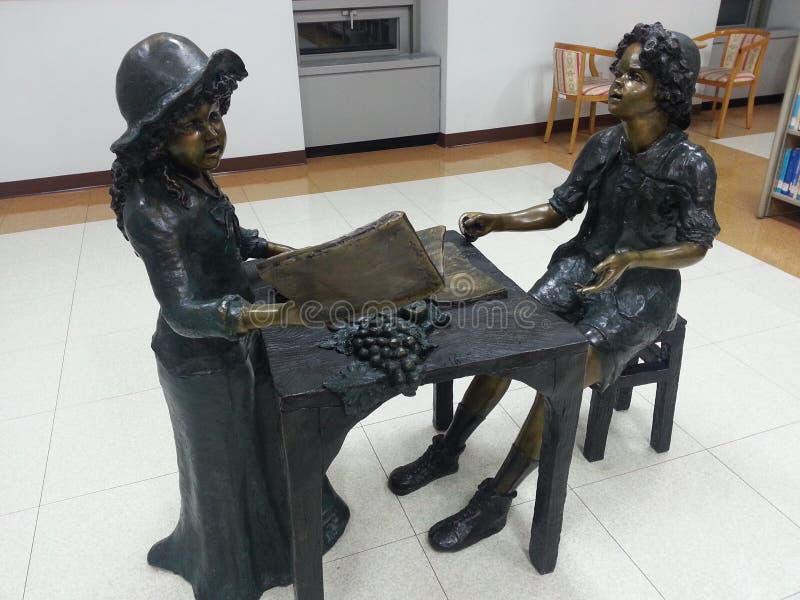 Escultura de dos estudiantes que hacen estudio del grupo imagenes de archivo