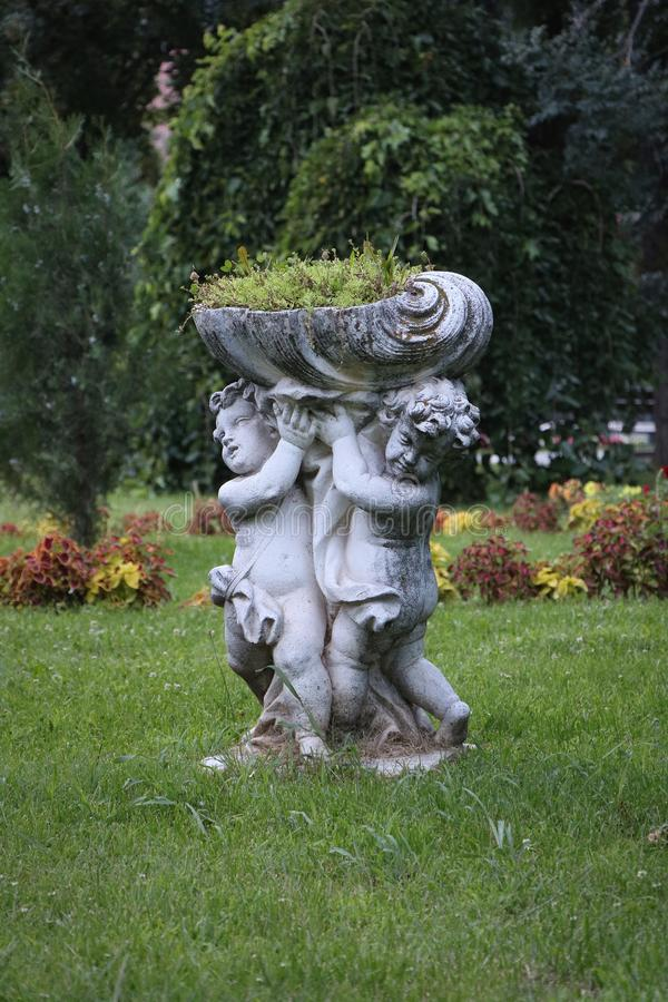 Escultura de duas flores do holdin das crianças imagem de stock