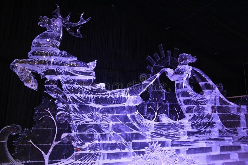 Escultura de gelo de um carro da rena com um motorista fotos de stock