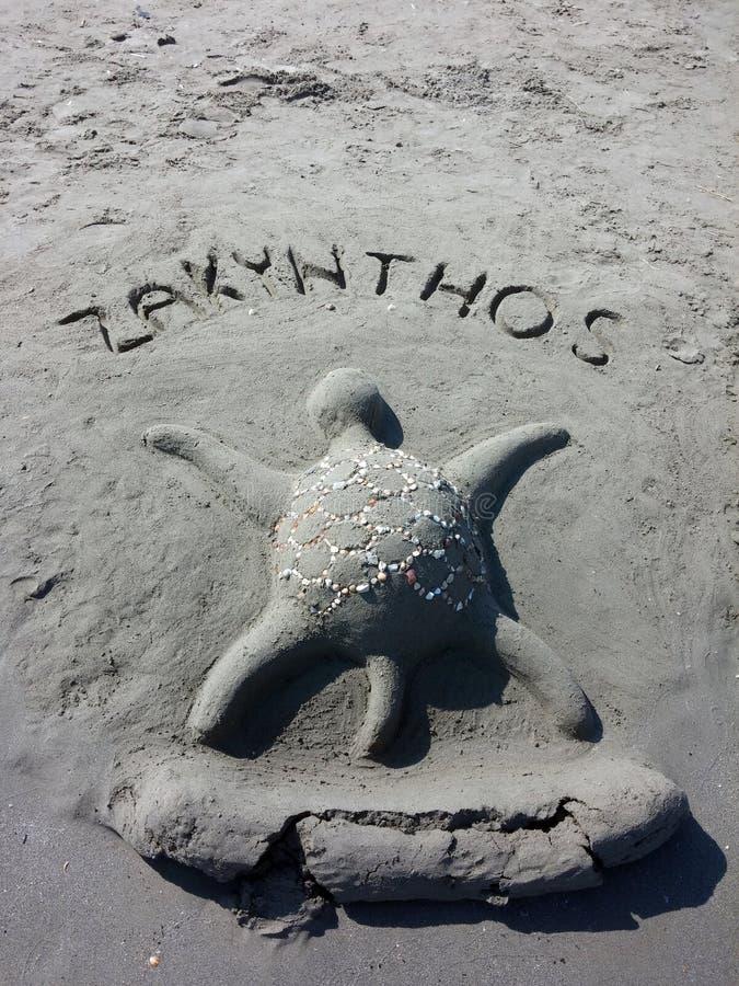 Escultura de la arena de una tortuga en una playa foto de archivo